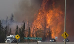 A heat haze distorts the picture as cars and trucks head south out of Fort McMurray, Alberta.
