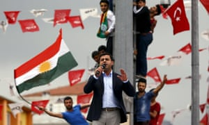 Selahattin Demirtas, co-chairman of the pro-Kurdish Peoples' Democratic Party (HDP), speaks as his supporters wave Kurdish (L) and Turkish national (R) flags in the background, during an election rally on 6 June.