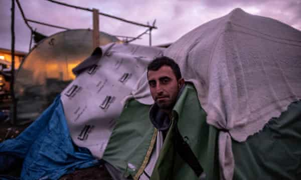 A man emerges from his tent hours before the camp is cleared.