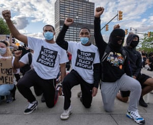 DETROIT, MICHIGAN – Following a night of confrontations protesters raise their fists as they knell in front of a police station in Detroit, Michigan on May 30, 2020 to protest the killing of George Floyd who died while a white officer held his knee on his neck for several minutes. - Demonstrations are being held across the US after George Floyd died in police custody on May 25.