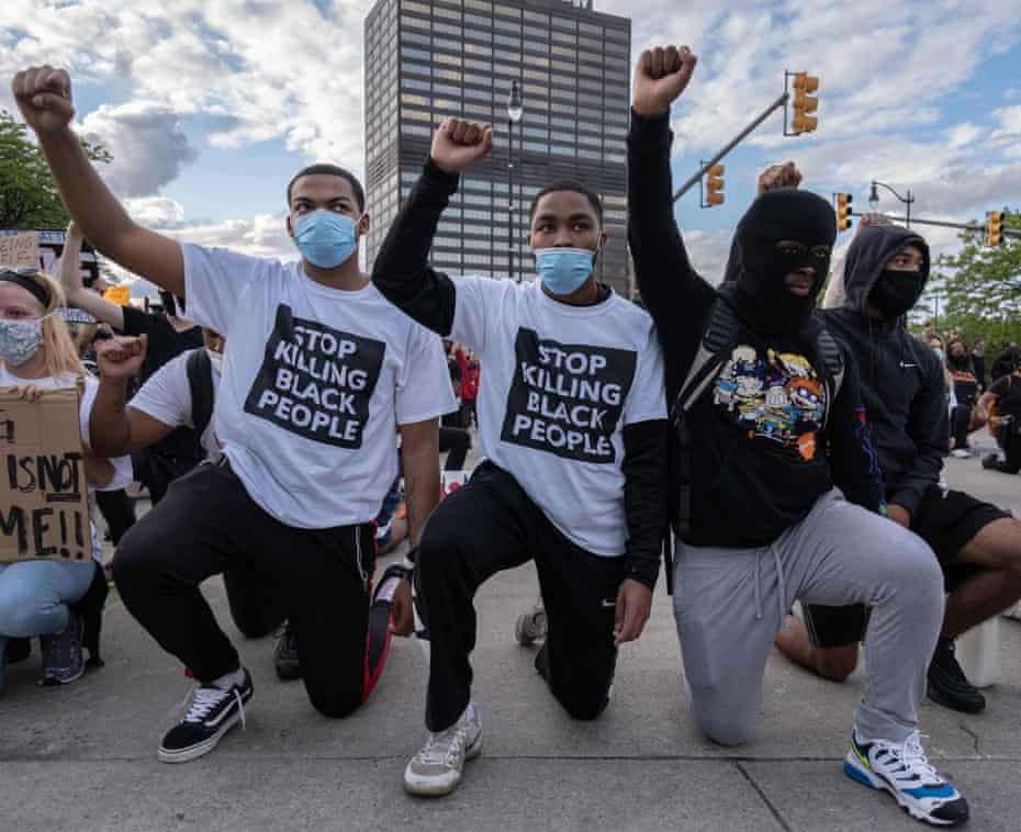 Protesters raise their fists as they kneel in front of a police station in Detroit, Michigan, on Saturday.