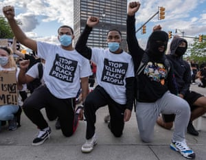 Following a night of confrontations protesters raise their fists as they kneel in front of a police station in Detroit, Michigan