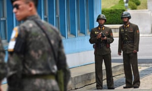 North Korean soldiers (right) look at the South side in the demilitarised zone on the border between North and South Korea.