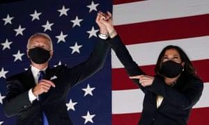 Joe Biden and Kamala Harris, raising each other's hands.