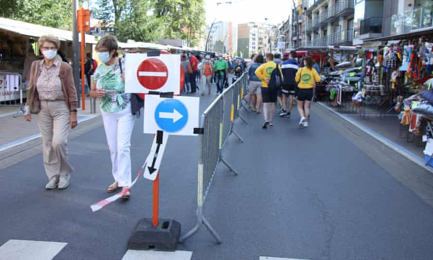 Pedestrians follow on-way signs to avoid close contact.