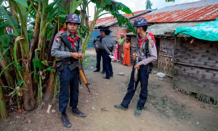 Myanmar police escort journalists during a government organized visit to Rohingya Muslims this week