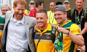 Prince Harry poses with Australian athletes taking part in the Invictus Games as Benjamin Yeomans holds up swimming trunks for the prince.