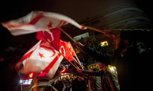 Protesters shout wave Turkish and Turkish Cypriot flags during a demonstration against Afrika in Nicosia.