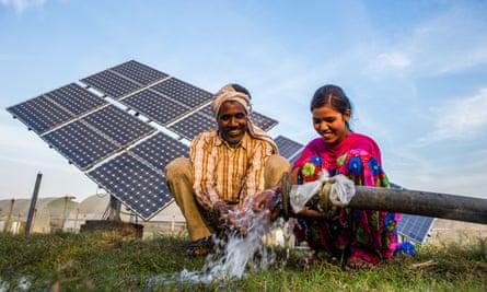 Sukhdev Vishwakarma and his daughter, Meenu, use water pumped from a solar water pump at a farms in Jagadhri.