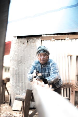 Lobsang, a carpenter who has travelled from Okuldhunga, planes a wooden beam