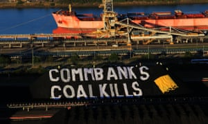 Greenpeace activists unveil a giant banner on Newcastle coal stockpiles, calling on the Commonwealth Bank to stop investing in coal