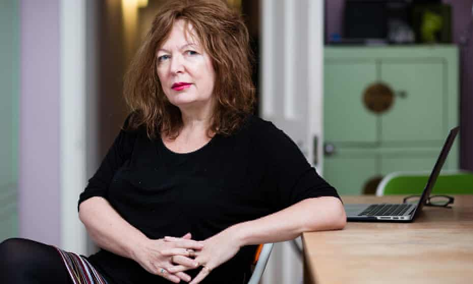 Suzanne Moore sitting, side on to a desk, with a laptop on it
