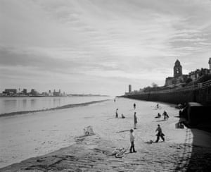 People gather on the beach at New Brighton