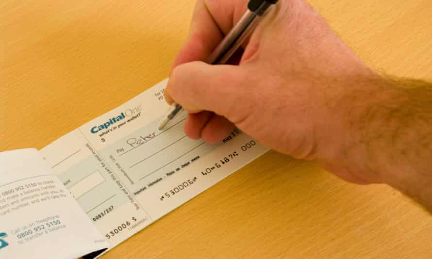 Man's hand writing a cheque