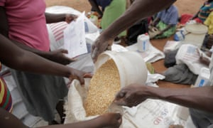 A woman pours food aid into a sack at a distribution point for Mafomoti primary school in Zimbabwe's Mwenezi district