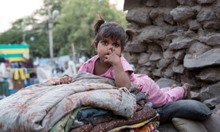 A young girl in a pink pyjama is laying on a pile of blankets and pillows on a market place on March 28, 2013 in Bijapur, India