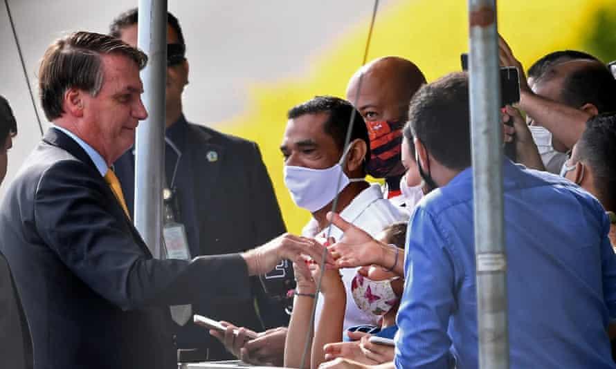 Brazil's president Jair Bolsonaro greets supporters in Brasilia, on April 13, 2021