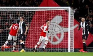 Mesut Ozil celebrates scoring their third goal.