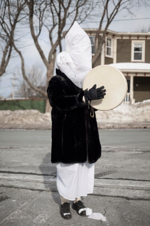 A mummerer, dressed in a white sheet, and dark coat, with their face covered, plays a bodhran on the streets of St John's, Newfoundland. The St John's Mummers Festival, with its mummers parade, is an example of the tradition's resurgence among a younger crowd. The festival started in 2009 and has taken place every year since, a few weeks before Christmas.
