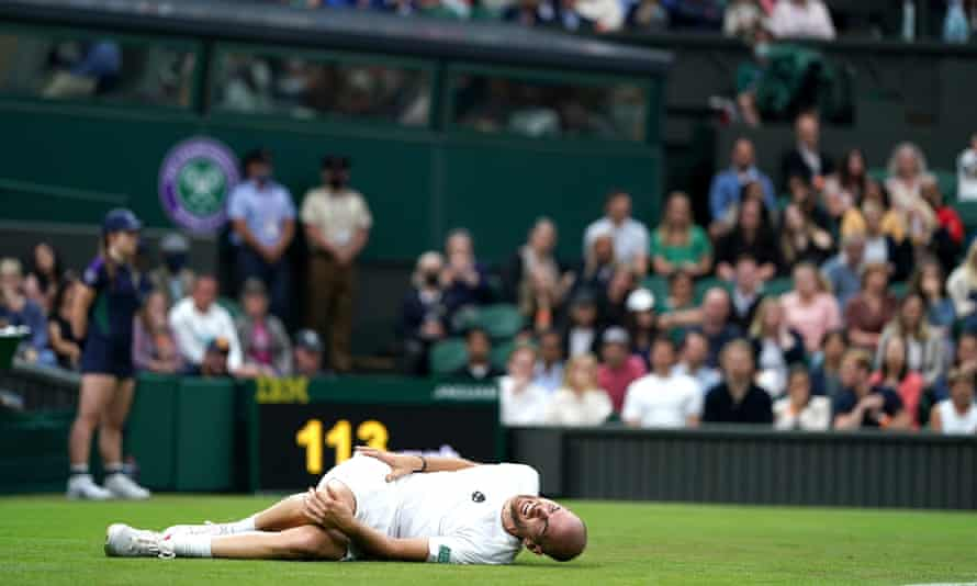 Adrian Mannarino writhes in pain after slipping on center court during his match against Roger Federer.