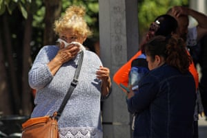 A woman covers her mouth trying to avoid 'the smell of death'.