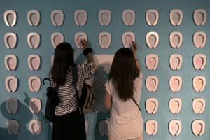 Visitors draw on toilet-shaped boards