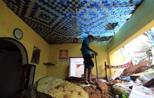A Sri Lankan mudslide survivor salvages belongings at a destroyed house in Kiribathgala on 29 May 2017