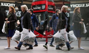 Shoppers in London loaded with bags as a red bus passes in the background