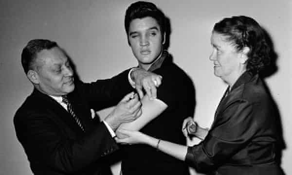 Elvis Presley standing between two medical staff receiving an injection in his arm