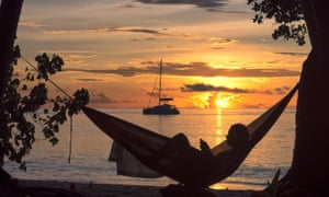 silhouette of a woman reading in hammock at sunset on tropical island