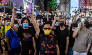 Demonstrators hold up mobile phones in Hong Kong