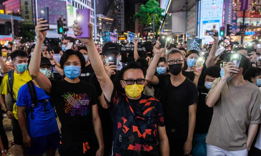 Demonstrators hold up mobile phones in Hong Kong