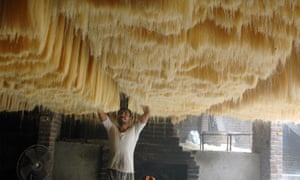 A worker checks the quality of dried noodles at a factory in Lahore