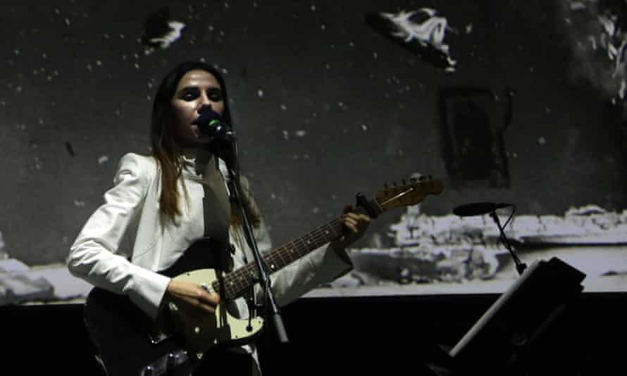 PJ Harvey performs in front of Seamus Murphy's photograph for The Hollow of the Hand.