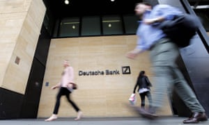 Pedestrians walk past the offices of Deutsche Bank in central London.