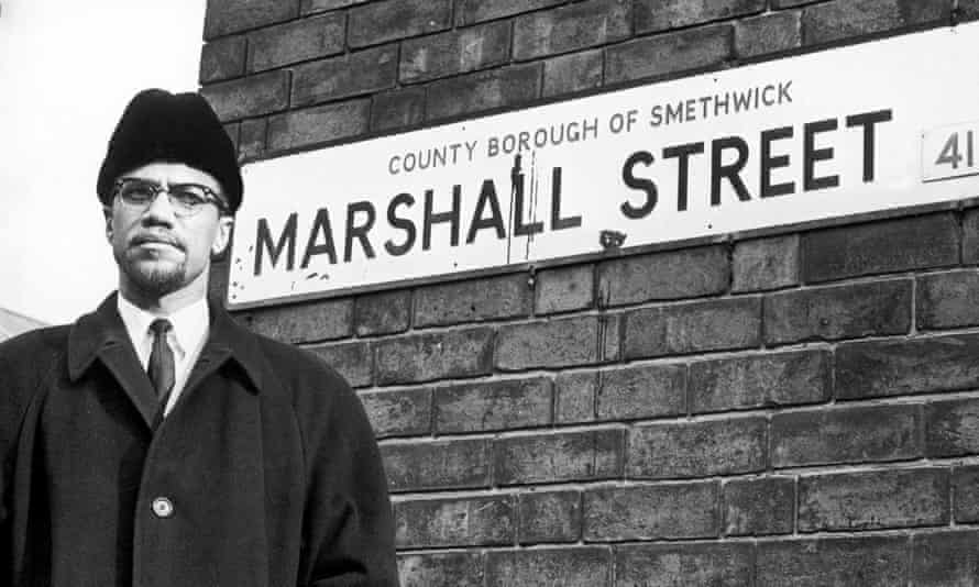 """Malcolm X African-American Muslim minister and human rights activist poses beside the street sign for Marshall Street in Smethwick during a visit to the Midlands. The human rights activist posed beside the nameplate, walked 50 yards up the street, smiled at a """"for sale"""" notice in the window of number 66 and returned to his car before being driven off. Malcolm X was assassinated nine days later on his return to the United States. 12th February 1965 (Photo by Birmingham Post and Mail Archive/Mirrorpix/Mirrorpix via Getty Images)"""