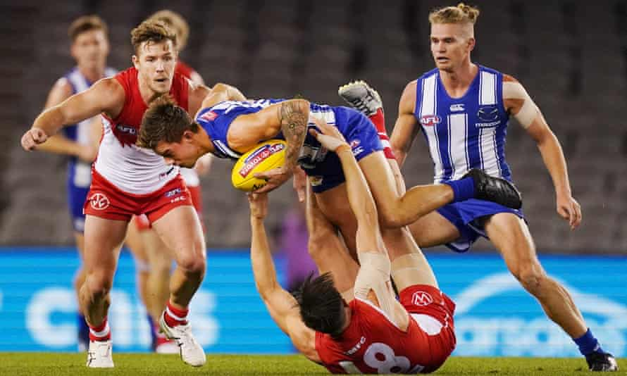 Callum Sinclair tackles Jy Simkin during the 2020 Round 3 AFL match between the North Melbourne Kangaroos and the Sydney Swans