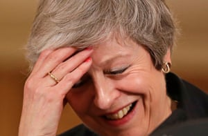 Theresa May holds her head in her hand at a press conference.