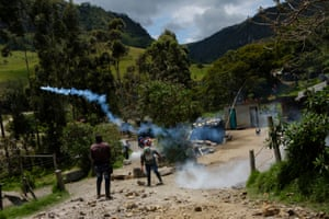 Kokonuko men return tear gas canisters fired at them by police at Aguas Tibias.