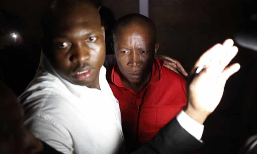 Julius Malema, dressed in red, is guarded, after leaving the parliament.