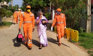 Disaster response staff escort a resident from housing near the LG Chem plant in India where 11 people have died.
