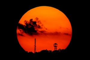 The setting sun is seen behind a look-out tower 109 kms northeast of Budapest