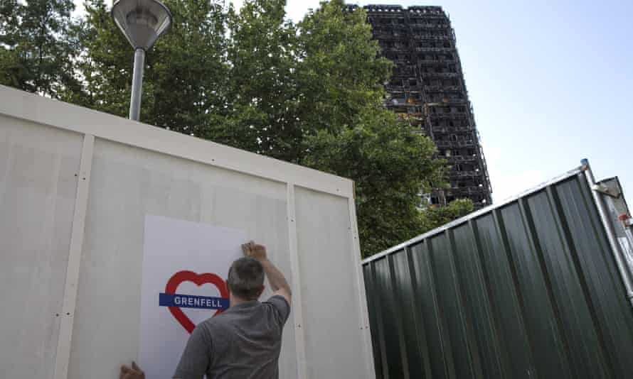 Posters are put up near to the charred shell of Grenfell Tower after the fire which killed 71 people.