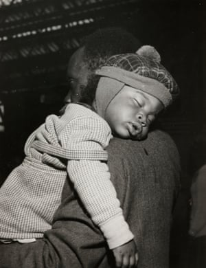 A child takes a nap after a long journey to Victoria station in London