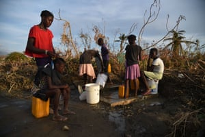 Haitians pump water from a cistern next to the road, in the commune of Chadonyer, in Les Cayes
