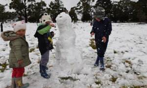 Beau, Noah and Lily Bartolo play with a snowman in a snow covered field in the town of Mittagong, New South Wales, Australia.