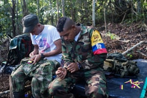 Guerrilla fighters sow Colombian flags onto their uniforms