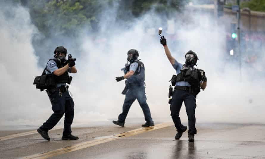 A police officer throws a teargas canister towards protesters in Minneapolis, Minnesota, on 26 May.