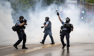 A police officer throws a teargas canister towards protesters.