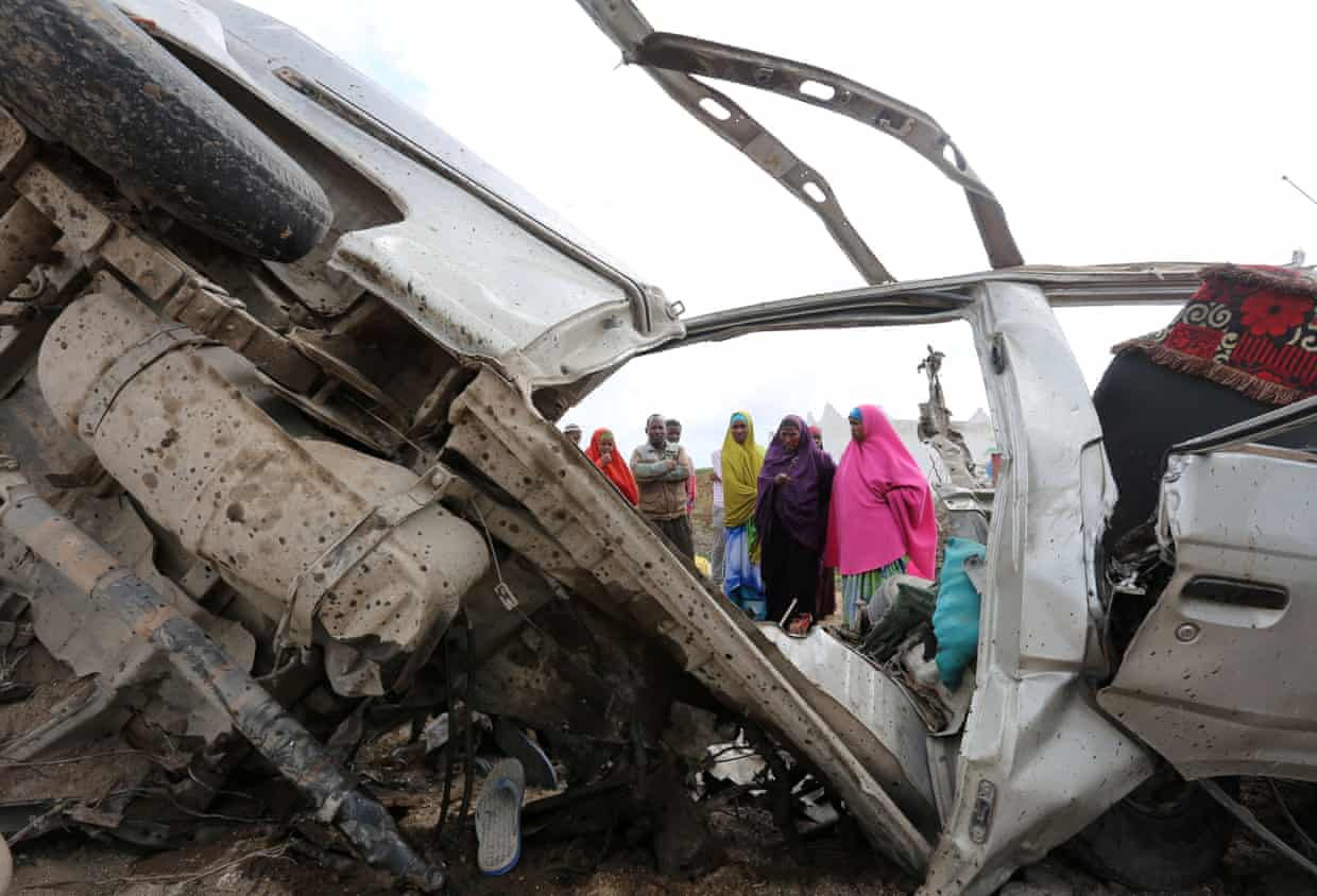 Locals look at the wreckage of a minibus destroyed in a roadside bomb in Lafoole village near Mogadishu, 30 June 2016.